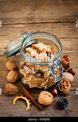 Gingerbread Christmas cookies stars in the glass jar with Christmas spices and decor close up - Stock Photo