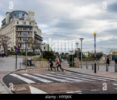 Two Teenagers on scooters & pedestrian crossing in front of  Park Inn Palace by Radisson. Southend-on-sea, Essex,England - Stock Photo