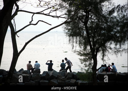 People watch the sun go down over the Malabar Coast from the shore at Fort Cochin. - Stock Photo