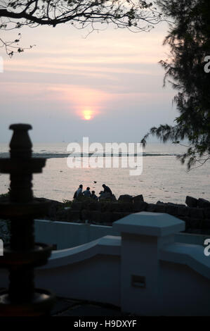 People watch the sun go down over the Malabar Coast from the shore at Fort Cochin, Kerala, India. - Stock Photo