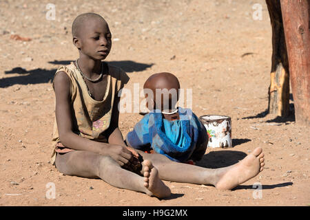 Children of indigenous Himba tribe in traditional clothes are playing in the sand at Kunene Region of Namibia - Stock Photo