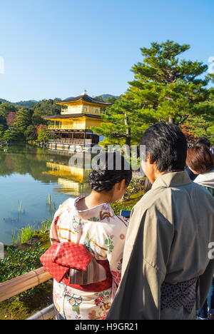 japanese couple by temple of the golden pavilion, Kyoto, Japan - Stock Photo