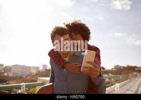 Kiss blowing, piggy back riding girl taking a selfie of them while sitting on her boyfriend back holding on with - Stock Photo