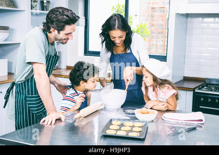 Happy family cooking biscuits together - Stock Photo