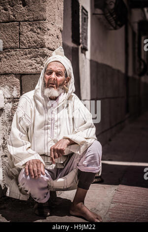 A portrait photograph of an elderly traditional Moroccan man in tradition clothes seated in a street in Morocco, - Stock Photo