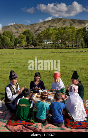 Kazakh family in traditional clothes praying before eating at a picnic in Saty Kazakhstan - Stock Photo