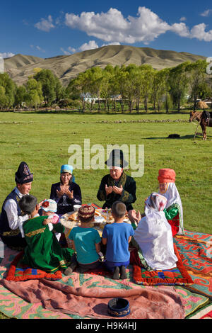 Kazakh family in traditional clothes praying before a picnic meal in pastureland at Saty Kazakhstan - Stock Photo