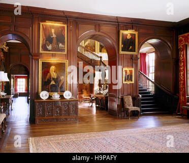 View of the entrance Hall at Antony showing the staircase, three arches , stained oak panelling, paintings and early - Stock Photo