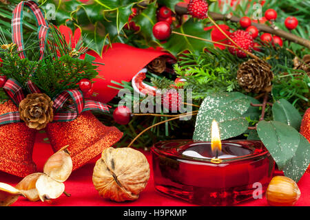Red heart shaped candle burning on a table decorated for christmas with glitter bells, berries and holly - Stock Photo