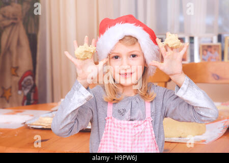 Young girl with Christmas hat holding dough in her hands - Stock Photo