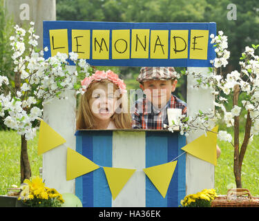 Two little kids are selling lemonade at a homemade lemonade stand on a sunny day with a sign for an entrepreneur - Stock Photo