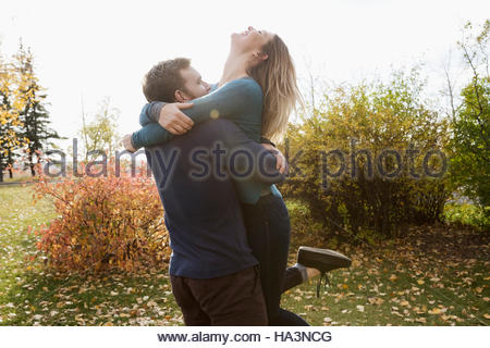 Playful couple laughing and hugging in autumn park - Stock Photo