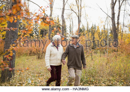 Senior couple walking holding hands in autumn woods - Stock Photo