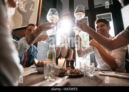 Group of young people making a toast at restaurant. Men and women sitting at a table in cafe and toasting wine. - Stock Photo