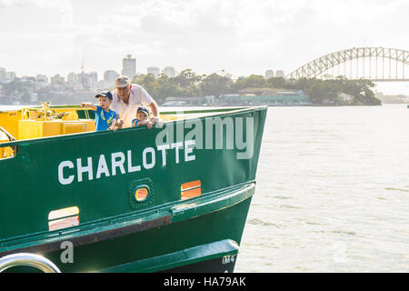 A grandad or older dad with two children on a ferry in Sydney Harbour - Stock Photo