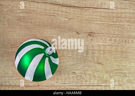 green glass Christmas ball on a light wooden background. - Stock Photo