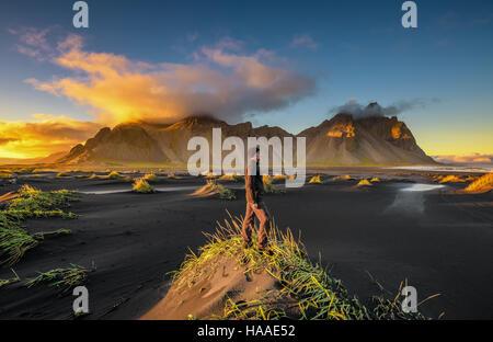 Hiker enjoying sunset at  Vestrahorn (Batman Mountain) and its black sand beach in Iceland - Stock Photo