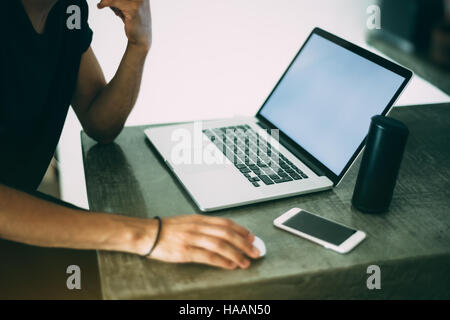 View of hands of a man in black t-shirt working with modern laptop standing on concrete table of cafe, mobile phone - Stock Photo