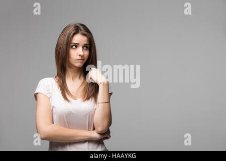 Portrait of contused thinking brunette woman. Studio shot on gray background - Stock Photo