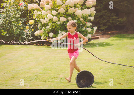 Young girl playing in the garden spraying water from the hose - Stock Photo