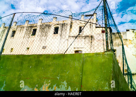 Green wall of sports ground topped with wire fence  in central Havana dilapidated building behind against blue sky - Stock Photo