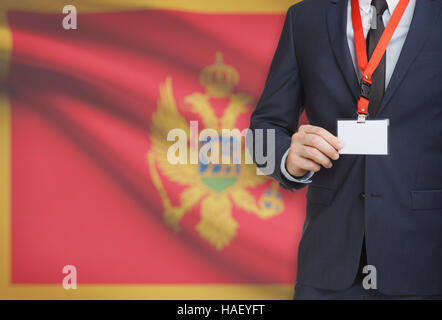 Businessman holding name card badge on a lanyard with a flag on background - Montenegro - Stock Photo