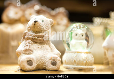 Cute white Christmas teddy bear made of porcelain is on the shelf in the background other xmas toys - Stock Photo