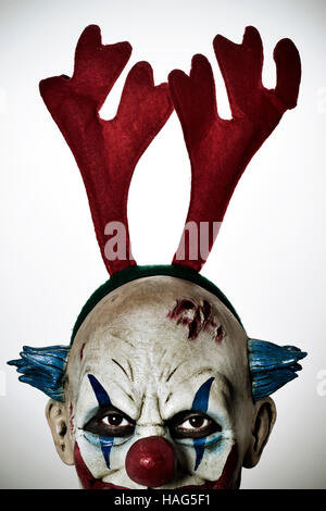 closeup of a scary evil clown wearing a reindeer antlers headband staring at the observer - Stock Photo