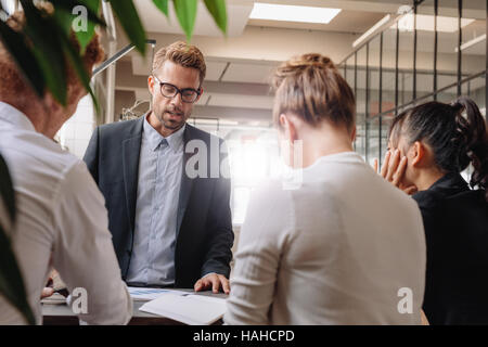 Businessman explaining new business strategy to colleagues. Group of business people having meeting in modern office. - Stock Photo