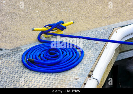 Blue mooring rope tied to yellow cleat - Stock Photo