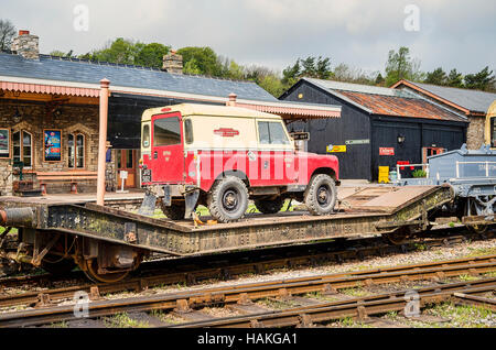 Old Landrover vehicle being transported by rail low-loader freight truck on the South Devon Railway - Stock Photo