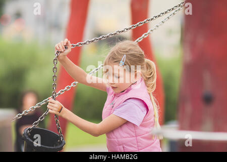 Young girl playing with bucket on playground - Stock Photo