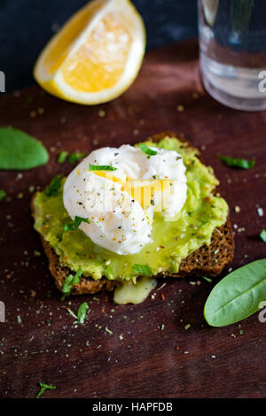 Mashed avocado and poached egg on toasted rye bread. Healthy breakfast, healthy snack - Stock Photo