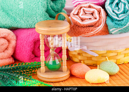 Spa set with colorful towels, candles and sand glass on bamboo background. - Stock Photo