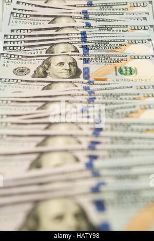 Many hundred dollar cash banknotes spread on surface - Stock Photo