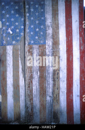 Weathered flag painting  on fence in New York City - Stock Photo