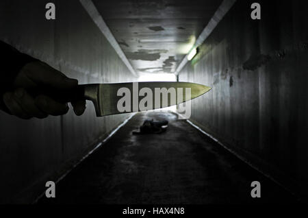 Man hand holds a knife over a murder victim in a dark tunnel. Violence against women concept. Real people, copy - Stock Photo