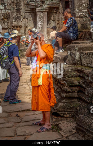 A Buddhist monk on vacation at Angkor Thom takes photos of the ruins in Siem Reap, Cambodia. - Stock Photo