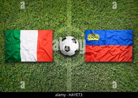 Italy vs. Liechtenstein flags on a green soccer field - Stock Photo
