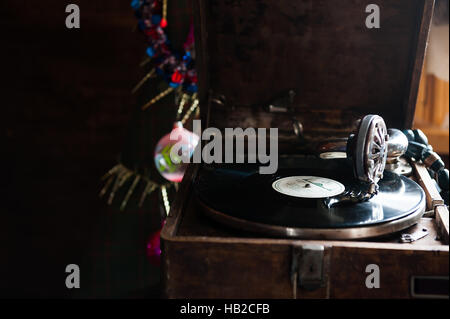 Gramophone playing a record. with vinyl on background decorations, cap, tree and bright lights - Stock Photo