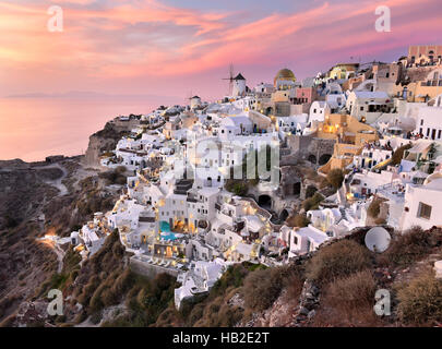 Oia Village in Cycladic Architecture style in Santorini, Greece during a pink sunset. - Stock Photo