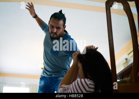 Social issues, abuse and aggression on women, young drunk man hitting and beating woman at home after drinking alcohol. - Stock Photo