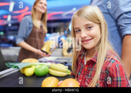 Small girl helping doing the shopping - Stock Photo