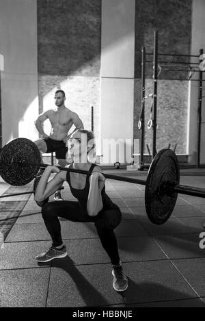 Concentrated athletic woman exercising with a barbell - Stock Photo