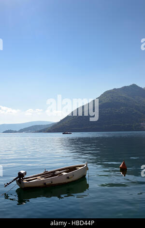 Small  boat on moorage at smooth sea surface near Perast, Kotor Bay, Montenegro - Stock Photo