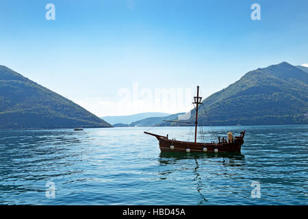 Single boat at smooth sea surface near Perast, Kotor Bay, Montenegro - Stock Photo