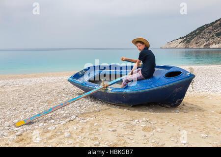 Teenage boy rowing in boat on greek beach - Stock Photo