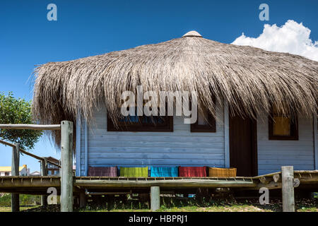 Typical brightly colored hous on the picturesque beach in Punta del Diablo, popular tourist place in Uruguay - Stock Photo