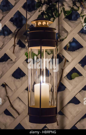 Candle lantern In snow at twilight - Stock Photo