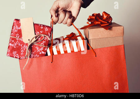 closeup of the hand of a young caucasian woman with her fingernails painted red holding a red shopping bag full - Stock Photo